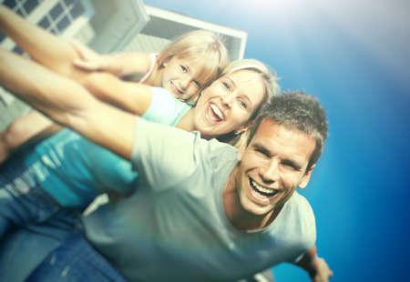 happy families: Familia sonriente feliz con el ni�o sobre fondo casa Foto de archivo