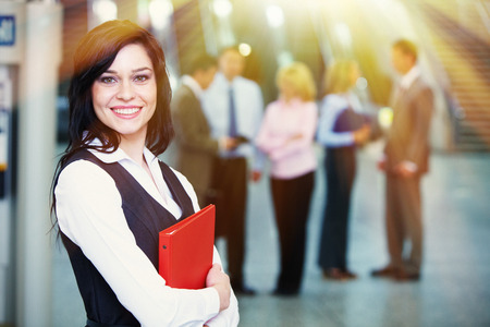 team leader: Bussinesswoman with red tablet over team background Stock Photo