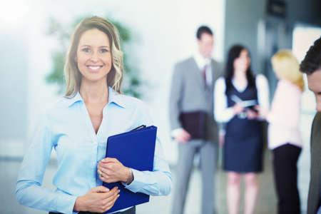 profesionálové: Bussinesswoman s černým tabletu přes týmu pozadí
