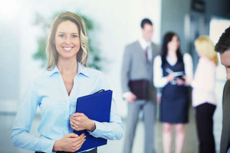Bussinesswoman with black tablet over team background Stock Photo - 22724464