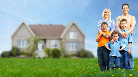 estate: Happy family near new house. Real estate. Stock Photo