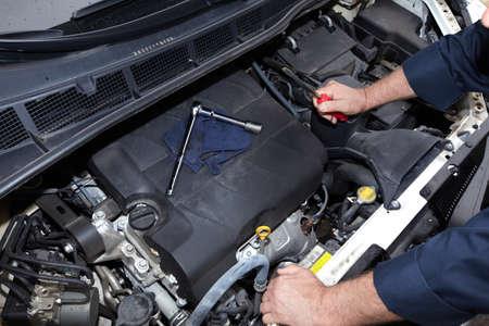techniek: Handen van automonteur met moersleutel. Auto reparatieservice.