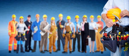 Worker with a tool belt. Over blue background. photo