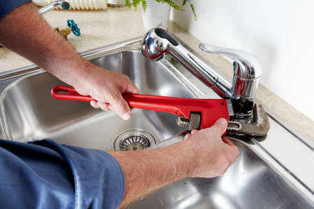 RENOVATE: Hands of professional Plumber with a water tap and wrench. Stock Photo