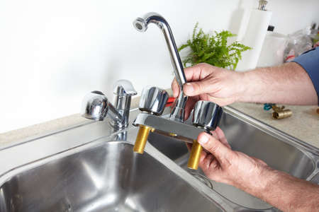 Hands of professional Plumber with a water tap. Stock Photo - 22871111