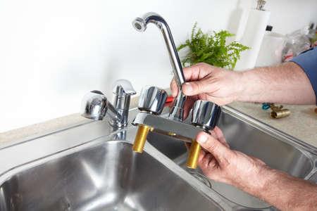 fontanero: Manos de fontanero profesional con un grifo de agua. Foto de archivo