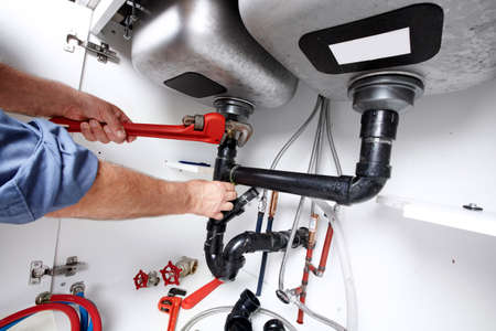 wrench: Hands of professional Plumber with a wrench. Clogged sink.