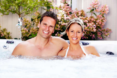 whirlpools: Happy couple relaxing in hot tub. Vacation. Stock Photo