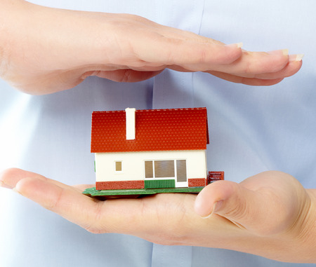 Hands holding Family house model. Real estate background. Stock Photo - 22770538