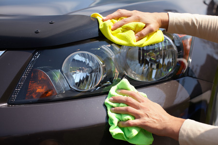 wash: Hand with microfiber cloth cleaning car.