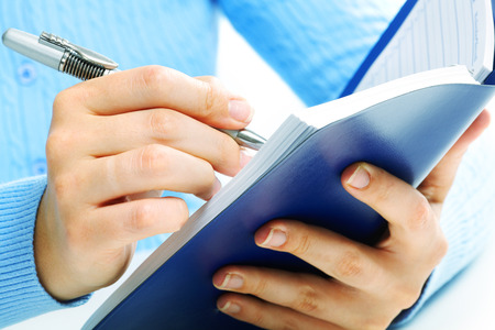 Hands of business woman writing in agenda. Stock Photo - 22770511
