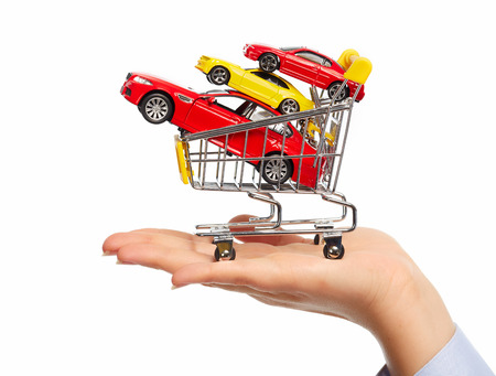 New car in shopping cart. Auto dealership concept background. photo