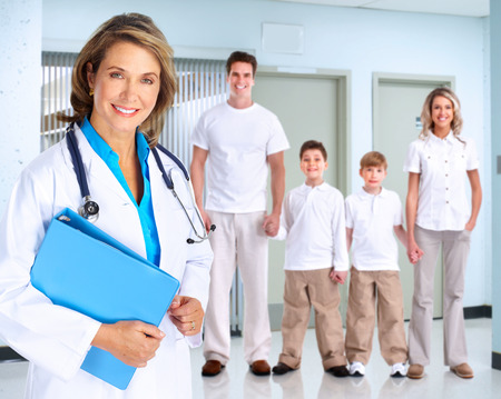 hospital background: Smiling family doctor woman with stethoscope. Health care.