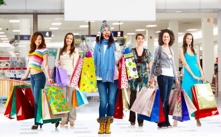 Young women group with shopping bags in shopping center photo