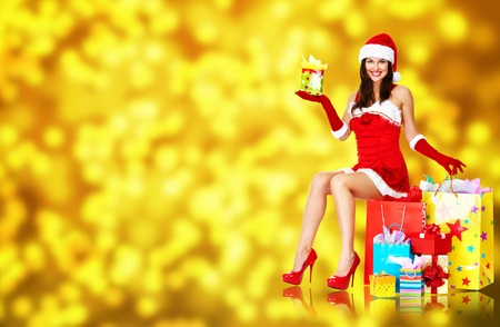 Beautiful Girl with Christmas gifts over Xmas background. photo