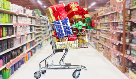 boxing day sale: Shopping cart with gifts in supermarket background Stock Photo