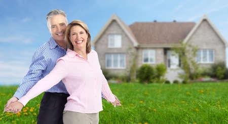 Senior couple near new home. Real estate background.