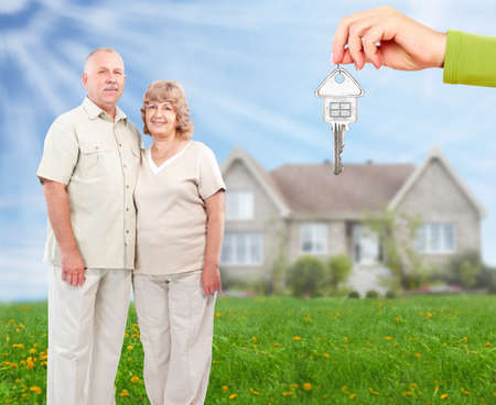 Senior couple near new home. Real estate background. photo