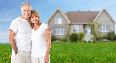 nieruchomosci: Starszy para w pobliżu nowego domu. Tło nieruchomości. Zdjęcie Seryjne