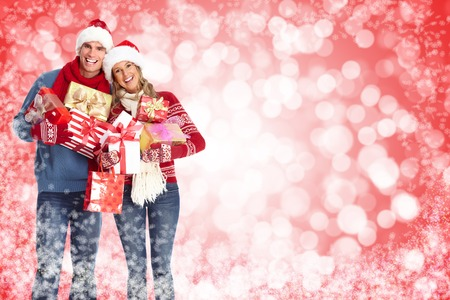 Happy christmas couple over red snowy background. Stock Photo - 24051245
