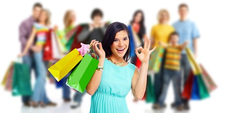 boxing day sale: Woman with shopping bags over people group background Stock Photo