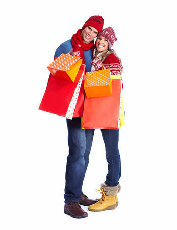 winter fashion: Happy couple with christmas shopping bags isolated over white background
