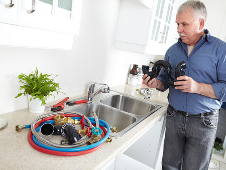 Plumber in kitchen with a wrench  Foreman  photo