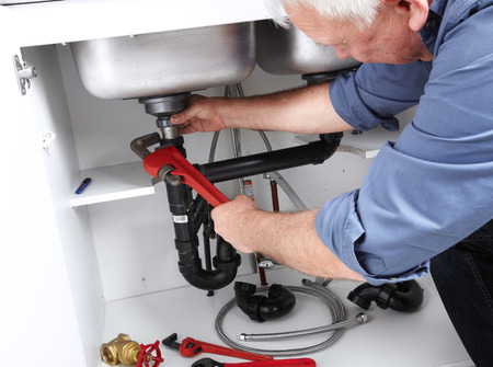 Hands of professional Plumber with a wrench  Clogged sink  photo