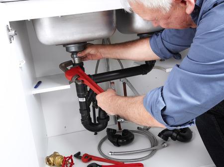 fontanero: Manos de fontanero profesional con un fregadero llave obstruido