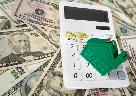 fees: House money and calculator. Mortgage concept background.