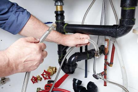 desague: Manos de fontanero profesional con una llave. Fregadero atascado. Foto de archivo
