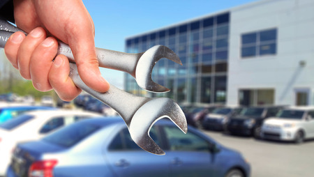 car shop: Hand of professional Auto mechanic with wrench.