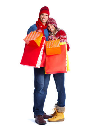 winter fashion: Happy couple with christmas shopping bags isolated over white background.
