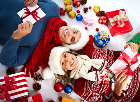 Happy couple with christmas gifts relaxing at home photo