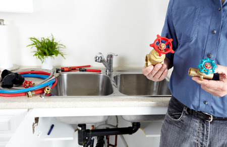 Hands of professional Plumber with a water tap. photo