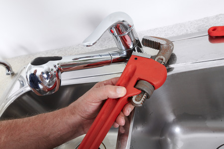 Hands of professional Plumber with a water tap and wrench. photo