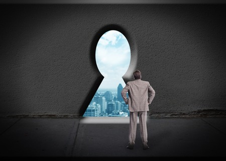 Businessman looking through keyhole. Access for success. photo