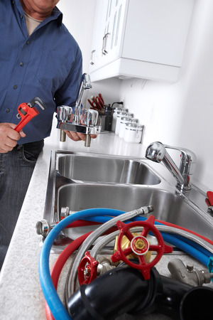 Hands of professional Plumber with a water tap and wrench  photo