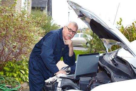 Car mechanic checking engine. Auto repair service. photo