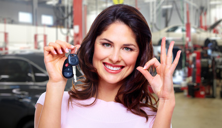 auto repair: Beautiful young woman with a car keys. Stock Photo