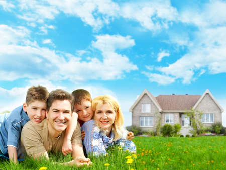 familias jovenes: Familia feliz cerca del nuevo hogar. Concepto de hipoteca.