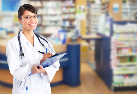 Beautiful smiling pharmacist woman in a drugstore photo
