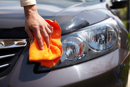 shine: Hand with microfiber cloth cleaning car.