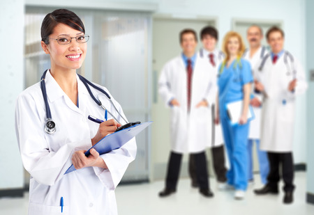 Beautiful smiling doctor woman over blue hospital background photo
