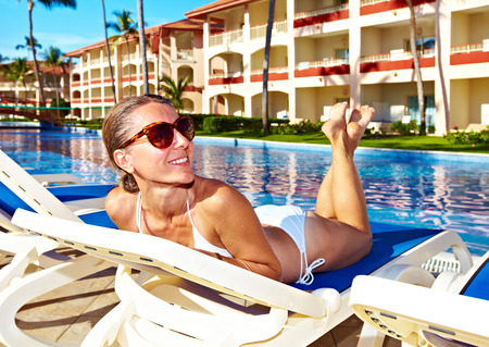 Woman relaxing near the pool. photo