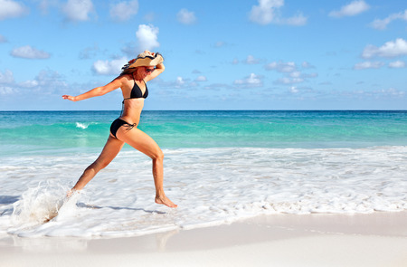 Happy woman running on the beach. Stock Photo