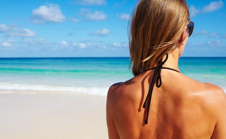 detras de: Detrás de la mujer en bikini en la playa. Foto de archivo