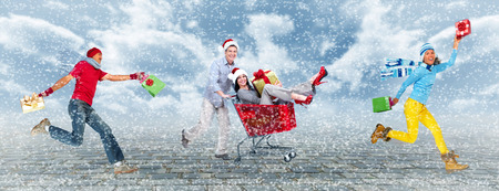 hurry up: Happy people running with Xmas gifts Stock Photo