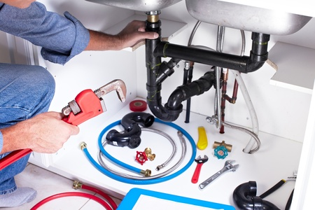 water sink: Plumber hands with a wrench. Stock Photo