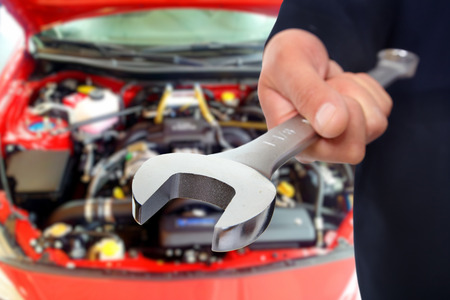 auto repair: Hand of car mechanic with wrench.
